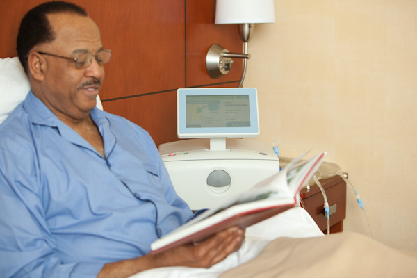 Photo provided by Baxter Canada - Man lays reading in bed while dialysis machine runs beside him